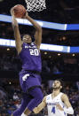 Kansas State's Xavier Sneed (20) goes up to dunk past Creighton's Ronnie Harrell Jr (4) during the first half of a first-round game in the NCAA men's college basketball tournament in Charlotte, N.C., Friday, March 16, 2018. (AP Photo/Gerry Broome)