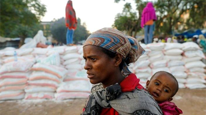 A woman carries an infant as she queues in line for food, at the Tsehaye primary school, in Shire, Tigray region, Ethiopia