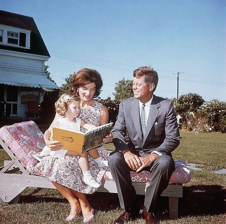 <p>Known for her classic style during her marriage to John F. Kennedy, Jackie reads to her daughter Caroline at the family's summer home in a classically-cut floral-patterned dress and matching pink pumps while the Senator looks on.<br></p>