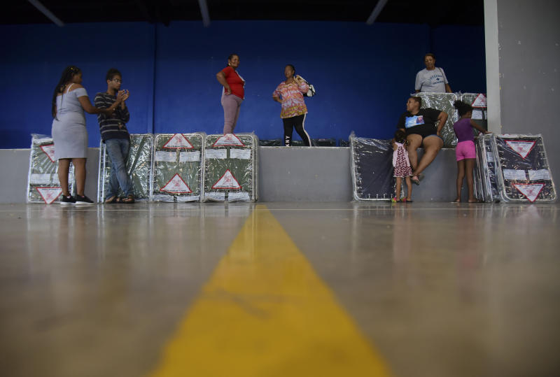 Residents arrive at the William Rivera Vocational School converted into a temporary shelter, before the arrival of Tropical Storm Dorian, in Canovanas, Puerto Rico, Wednesday, Aug. 28, 2019. Dorian became a Category 1 hurricane on Wednesday as it struck the U.S. Virgin Islands, with forecasters saying it could grow to Category 3 status as it nears the U.S. mainland as early as the weekend. (AP Photo/Carlos Giusti)