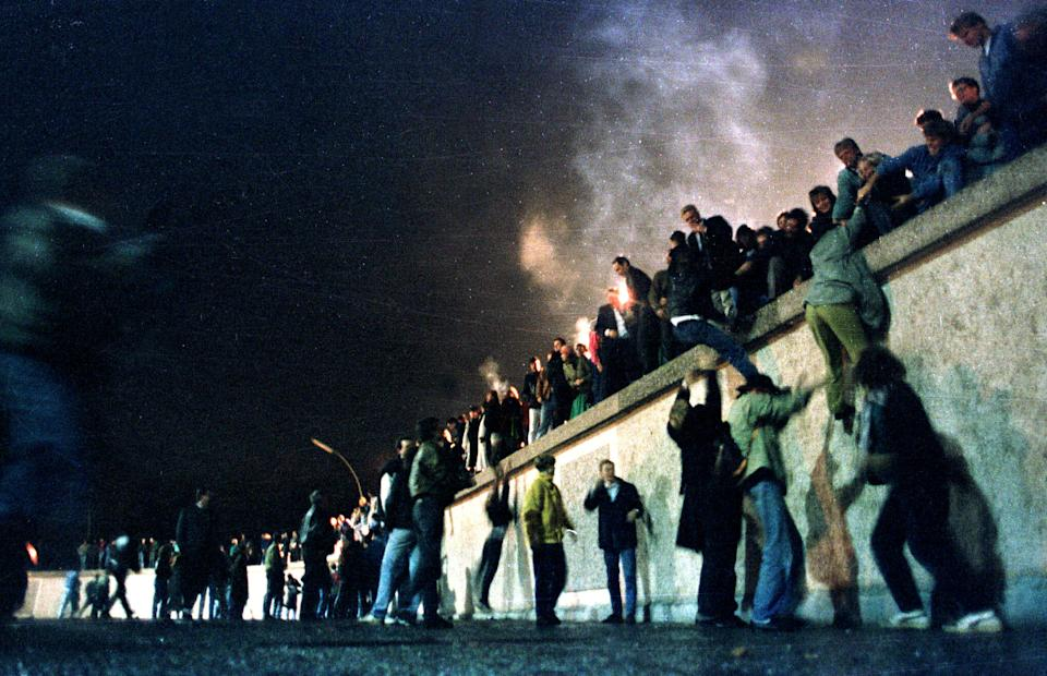 People climb the Berlin Wall at the Brandenburg Gate after the opening of the East German border Nov. 9, 1989. Nov. 9, 1989. (Photo: Herbert Knosowski/Reuters)