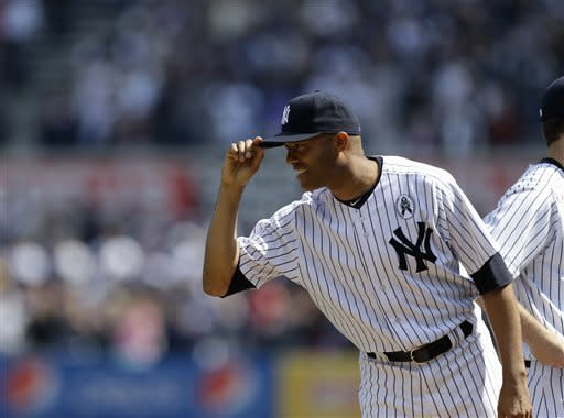 New York Yankees relief pitcher Mariano Rivera (42) tips his cap to Red Sox players at an Opening Day baseball game at Yankee Stadium in New York, Monday, April 1, 2013. (AP Photo/Kathy Willens)