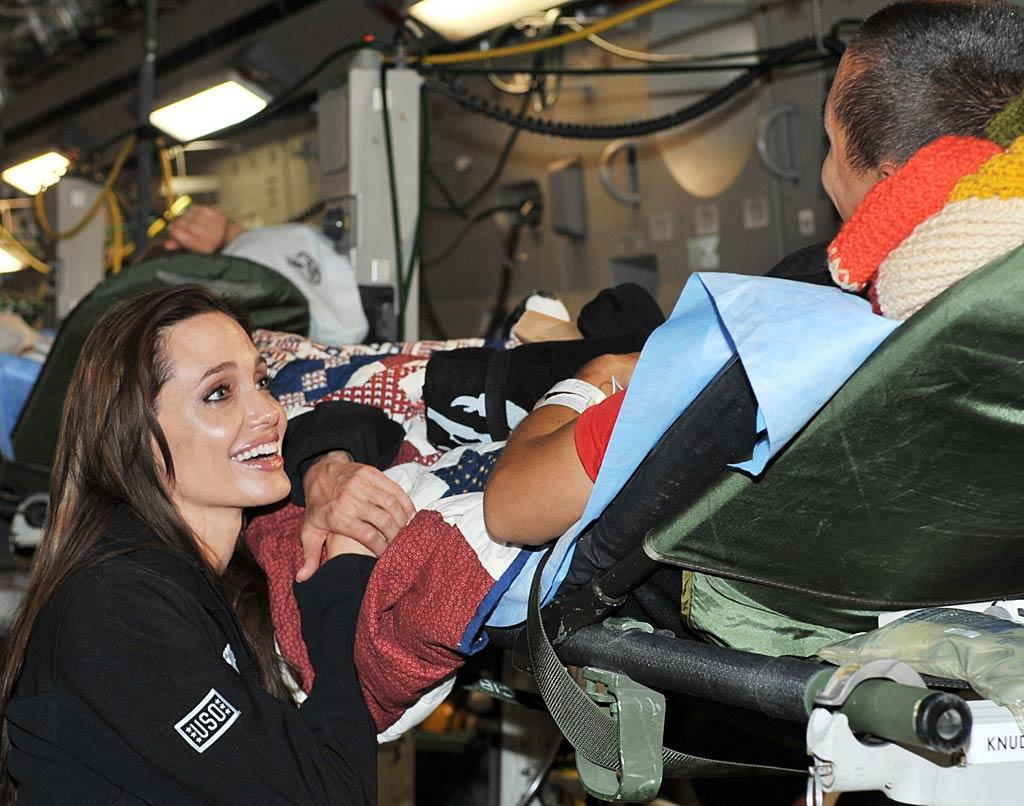 "Angelina Jolie put a smile on the faces of some wounded warriors she met with last week at Ramstein Air Base in Germany as they prepared to travel back to the U.S. for the first time since being injured. And they clearly put one on hers, too! <a href=""http://www.pacificcoastnews.com/"" target=""new"">PacificCoastNews.com</a> - May 13, 2011"