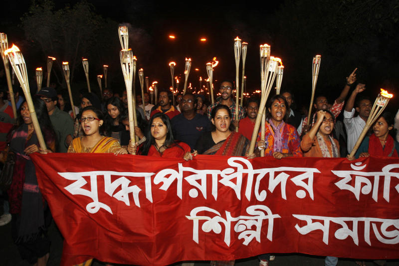 FILE - In this Wednesday, Feb .6, 2013 file photo, Bangladeshi people participate in a torch rally demanding death penalty for Jamaat-e-Islami, leader Abdul Quader Mollah in Dhaka, Bangladesh. Mollah, an assistant secretary of Jamaat, was found guilty of killing a student and a family of 11 and of aiding Pakistani troops in killing 369 others. Members of his party took to the streets in anger at his conviction, exploding homemade bombs and clashing with police. But they were soon overshadowed by thousands of protesters who flooded a major intersection in the capital, Dhaka, upset at what they said was a lenient verdict and inflamed by the image of Mollah smiling at journalists and holding up two fingers in a ''V'' sign as he left the court. Banner reads 'Hang war criminals. Cultural activists'. (AP Photo/Pavel Rahman)