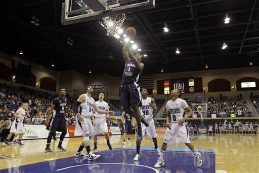 Brigham Young's Charles Abouo, above, shoots above San Diego's Chris Manresa, third from left, Dennis Kramer, fourth from left, Ken Rancifer (32), and Christopher Anderson (0) in the first half during an NCAA college basketball game Monday, Jan. 16, 2012, in San Diego. (AP Photo/Gregory Bull)