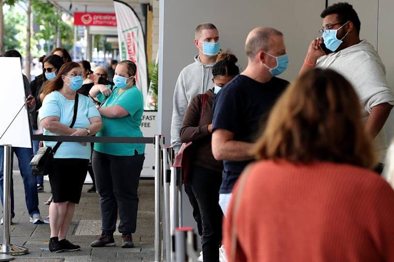 Customers are given face masks to wear before being allowed entry into the Apple Store in Perth. Source: AAP