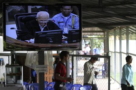 People enter the ECCC as a television screen shows Chea, in the outskirts of Phnom Penh