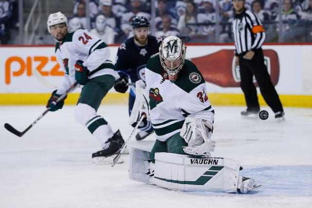 Minnesota Wild's goaltender Alex Stalock (32) saves the shot from the point as Wild's Matt Dumba (24) and Winnipeg Jets' Bryan Little (18) watch during the second period in Game 5 of an NHL hockey first-round playoff series in Winnipeg, Manitoba, Friday, April 20, 2018. (John Woods/The Canadian Press via AP)