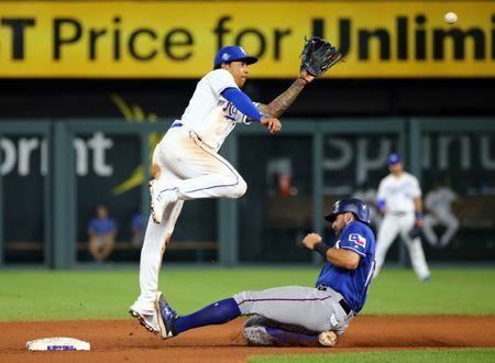 Jun 20, 2018; Kansas City, MO, USA; Kansas City Royals shortstop Adalberto Mondesi (27) jumps for the ball as Texas Rangers third baseman Joey Gallo (13) slides into second base in the eighth inning at Kauffman Stadium. Mandatory Credit: Jay Biggerstaff-USA TODAY Sports
