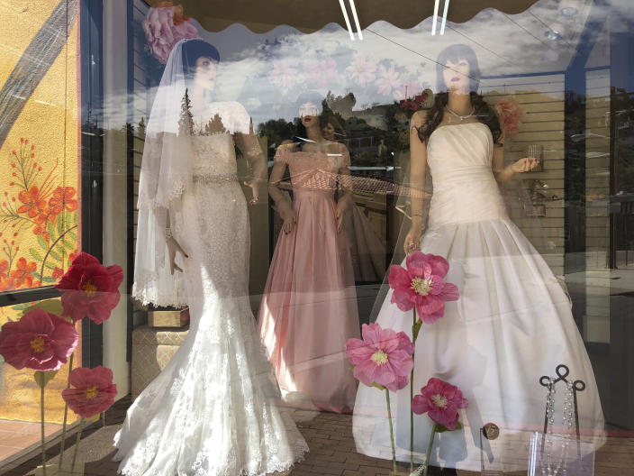 Mannequins in wedding gowns are seen in a window display on March 15, 2021, at a bridal store in Nogales, Ariz., that has been closed for nearly a year because of the pandemic. Like other border businesses, the store closed after its main customer base, Mexican day-trippers, were largely unable to come to the U.S. and shop after the U.S. partially closed its borders with Mexico and Canada in March 2020. (AP Photo/Suman Naishadham)