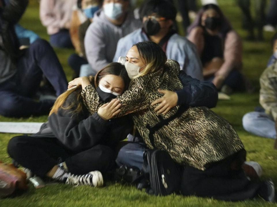 Group of girls sit hugging each other at protest