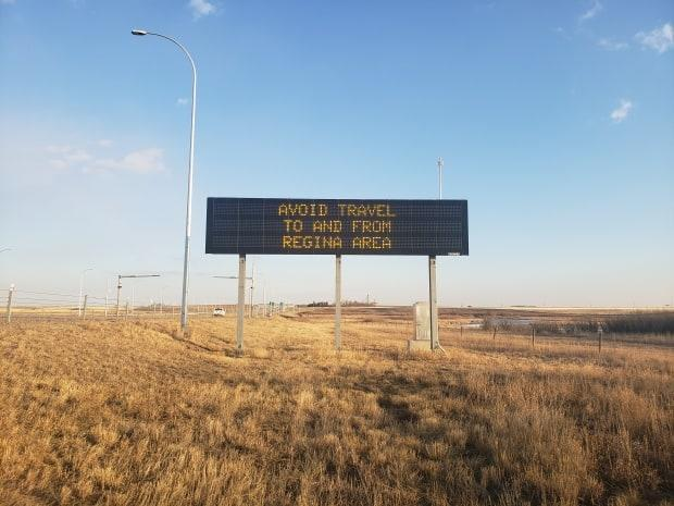 A sign shown before the winter storm hits southern Saskatchewan is reminding people to avoid the Regina area due to the increased COVID-19 concerns in the city. Meteorologist Terri Lang said people should avoid hitting the highways at all on Monday as a storm blows through the province.  (Submitted by Kenton de Jong - image credit)