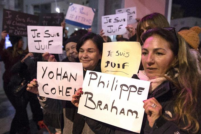 French-Israeli dual nationals holds signs naming the Jewish victims of Friday's attack on a supermarket in Paris during a remembrance ceremony in the coastal Israeli city of Netanya on January 11, 2015 (AFP Photo/Jack Guez)