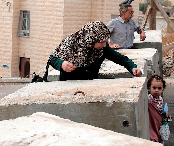 A Palestinian woman and child pass through concrete blocks installed by Israeli police at a checkpoint in the East Jerusalem neighbourhood of Jabal Mukaber (AFP Photo/Ahmad Gharabli)