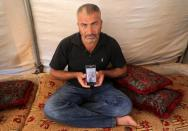 Issam Faysal Youssef, 40, displays a picture of his deceased cousin in Idlib