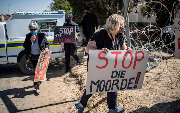 Demonstrators carry placards during a demonstration against farm attacks - AFP