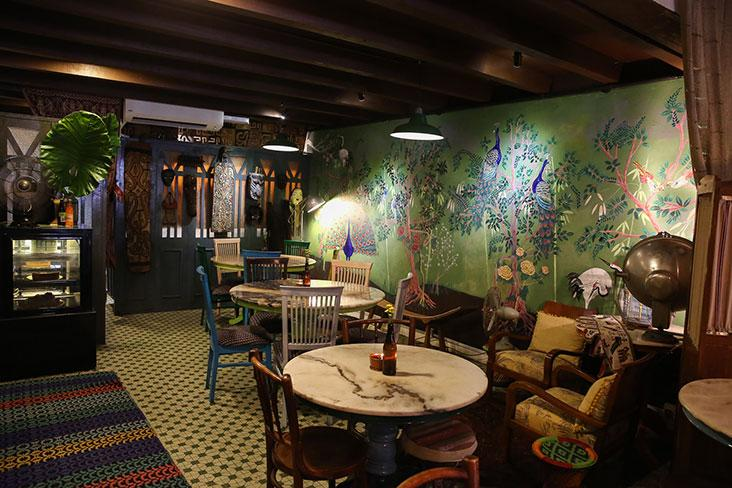 The bold and beautiful hand-painted mural with a Chinoiserie theme of exotic birds in a garden of trees and flowers take centre stage in the restaurant