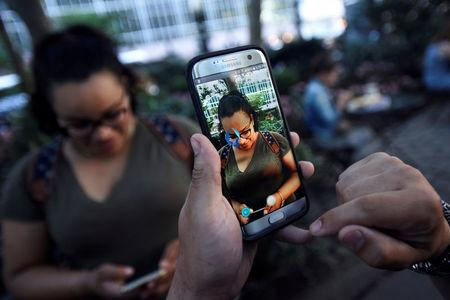 "A Pokemon appears on the screen next to a woman as a man plays the augmented reality mobile game ""Pokemon Go"" by Nintendo in Bryant Park in New York City, U.S. July 11, 2016. REUTERS/Mark Kauzlarich/File Photo"