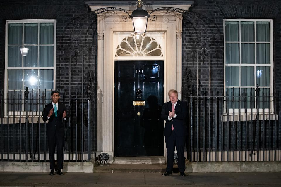 Prime Minister Boris Johnson (right) and Chancellor Rishi Sunak outside 10 Downing Street, London, joining in with a national applause for the NHS to show appreciation for all NHS workers who are helping to fight the Coronavirus. (Photo by Aaron Chown/PA Images via Getty Images)