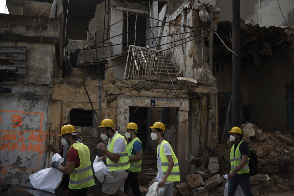 Volunteers from the American University of Beirut walk next to destroyed buildings on a neighborhood near the site of last week's explosion that hit the seaport of Beirut, Lebanon, Thursday, Aug. 13, 2020. (AP Photo/Felipe Dana)