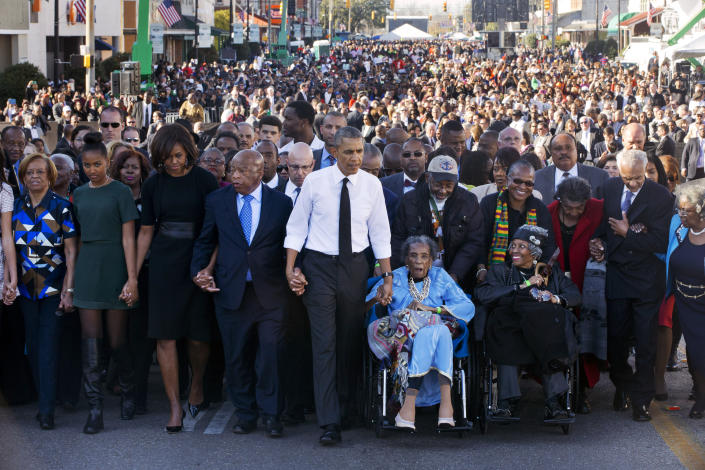 """FILE - In this March 7, 2015, file photo, President Barack Obama, center, walks as he holds hands with Amelia Boynton Robinson, who was beaten during """"Bloody Sunday,"""" as the first family and others including Rep. John Lewis, D-Ga., left of Obama, walk across the Edmund Pettus Bridge in Selma, Ala., for the 50th anniversary of """"Bloody Sunday,"""" a landmark event of the civil rights movement. From front left are Marian Robinson, Sasha Obama, first lady Michelle Obama, Obama, Boynton and Adelaide Sanford, also in wheelchair. (AP Photo/Jacquelyn Martin, File)"""