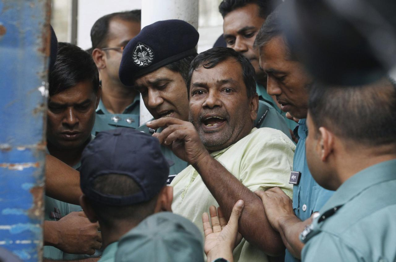 A prisoner reacts as police force him into a van after the verdict for a 2009 mutiny is announced, in Dhaka November 5, 2013. A special court in Bangladesh on Tuesday sentenced to death more than 150 people, from among hundreds of mutineers accused of murder and arson at the headquarters of the country's border guards in 2009. REUTERS/Andrew Biraj (BANGLADESH - Tags: CRIME LAW TPX IMAGES OF THE DAY)