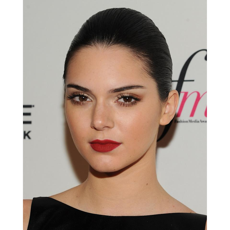 Even with a simple powdery complexion and nearly bare eyes, Jenner looks markedly different in a dusky red lip.