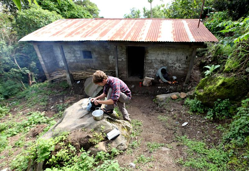 This 2010 photo provided by Living on One shows Chris Temple and Ryan Christofferson preparing food outside the dirt-floor hut where they lived for a summer in the village of Pena Blanca, Guatemala. They lived there with two other U.S. college students on $1 a day per person to experience firsthand issues related to rural poverty, then made a film about their experiences. (AP Photo/Living on One)