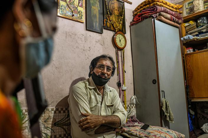 Jayanti Keshav Parmar, a tailor, at his home in Dharavi. His sewing machine sits idle, as no one in the neighborhood can afford to have new clothes stitched this year.