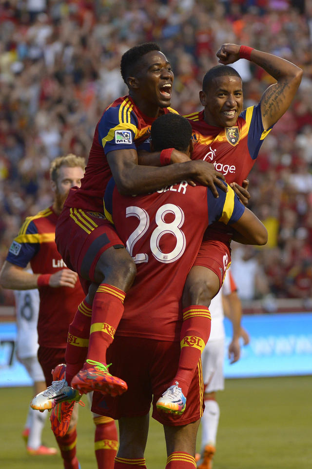 Real Salt Lake forwards Olmes Garcia (13) and Joao Plata (8) jump into the arms of defender Chris Schuler (28) after one of Schuler's two goals during the first half of an MLS soccer game against DC United, Saturday, Aug. 9, 2014, in Sandy, Utah. (AP Photo/The Salt Lake Tribune, Leah Hogsten)