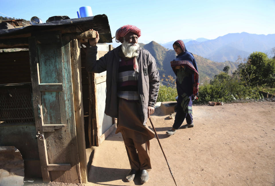 An elderly Indian Noordin, who alleges his son Altaf Hussain was killed by Pakistan army while ferrying ration supplies to one of the Indian army border posts, stands outside his house in Poonch, India, Wednesday, Dec. 16, 2020. The terrain is tough and the life of civilians living in the area is even tougher, with them often caught in the line of fire along the Line of Control, that for the past 73 years divided the region between the two nuclear-armed rivals of India and Pakistan. Over the last year, troops from the two sides have traded fire almost daily along the frontier, leaving dozens of civilians and soldiers dead. (AP Photo/Channi Anand)