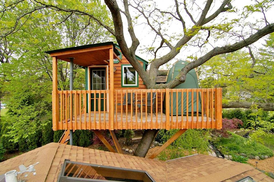"""<p>This sturdy cedar structure is located just 30 minutes from downtown Chicago. Perched 15 feet above ground, the treehouse overlooks an enchanting backyard garden, complete with a waterfall and koi pond. Inside, guests are treated to air conditioning as well as a fireplace.</p><p><a class=""""link rapid-noclick-resp"""" href=""""https://www.airbnb.com/rooms/440817"""" rel=""""nofollow noopener"""" target=""""_blank"""" data-ylk=""""slk:BOOK NOW"""">BOOK NOW</a> <strong><em>Enchanted Garden Treehouse</em></strong></p>"""