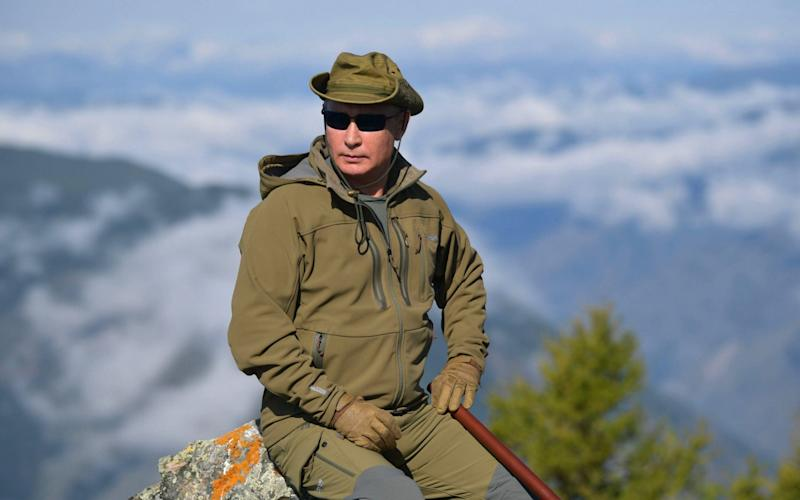 The Russian president pauses for a photograph at the top of a peak in Tyva he said was almost 6,500 feet high - REX