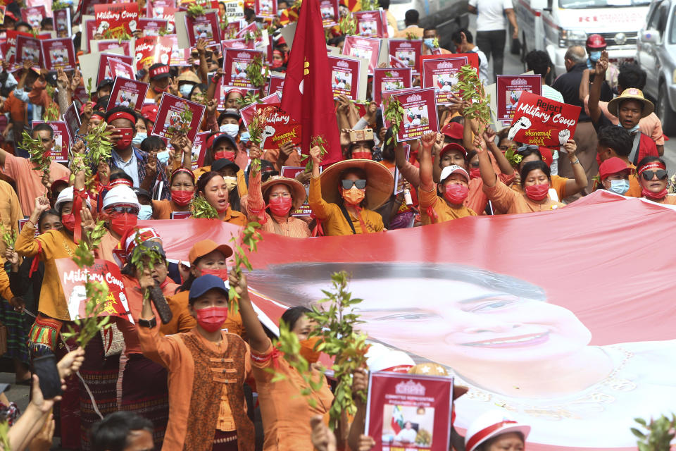 Protesters march with a giant banner with images of ousted leader Aung San Suu Kyi during an anti-coup protest in Mandalay, Myanmar, Sunday, Feb. 21, 2021. Police in Myanmar shot dead a few anti-coup protesters and injured several others on Saturday, as security forces increased pressure on popular revolt against the military takeover. (AP Photo)