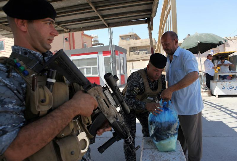 Iraqi security forces check people in an eastern district of Baghdad, on August 11, 2014 (AFP Photo/Amer Al-Saedi)