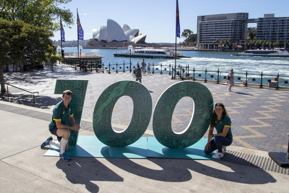 Australian Olympians Edward Fernon, modern pentathlon, and slalom canoeist Jess Fox pose by a sign at a ceremony to mark 100 days before the start of the Tokyo Olympics in Sydney Wednesday, April 14, 2021. Olympics live sites will be held across Australia during the Olympic Games, from July 23 to Aug. 8 2021, taking advantage of the one hour time zone difference for Australians to watch athletes perform. (AP Photo/Mark Baker)