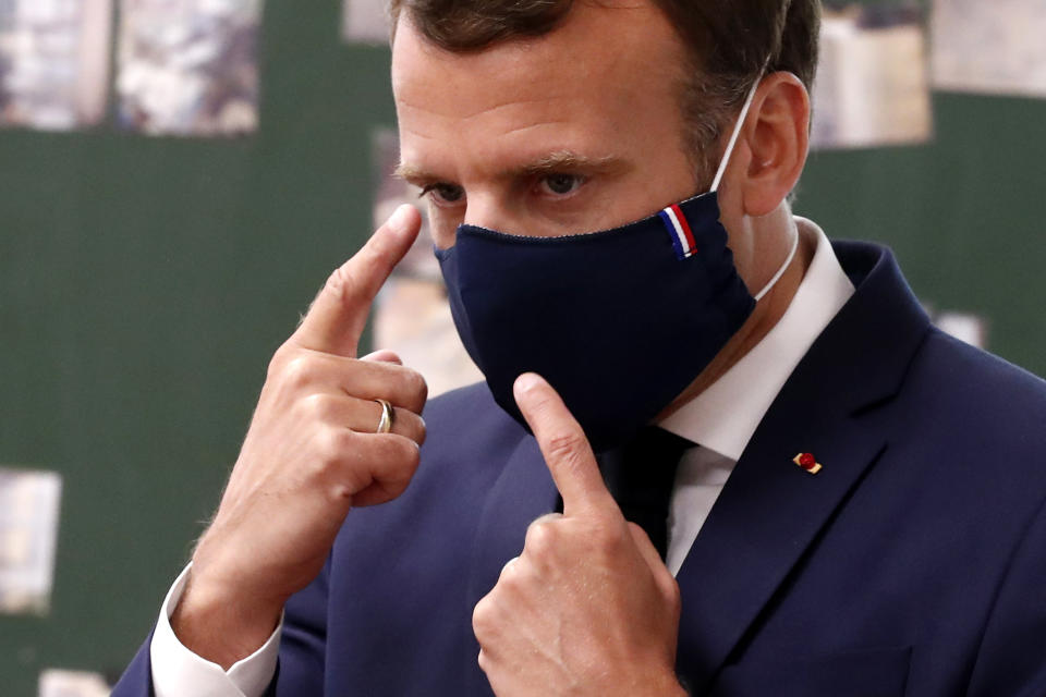 French President Emmanuel Macron wears a protective face mask as he speaks with schoolchildren at the Pierre Ronsard elementary school Tuesday, May 5 2020 in Poissy, outside Paris. Starting from May 11, all French businesses will be allowed to resume activity and schools will start gradually reopening. (Ian Langsdon, Pool via AP)