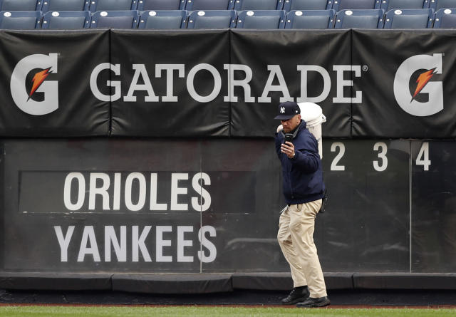 A worker snaps a cell phone photo of the tarp-covered field at Yankee Stadium as he carries a bucket back past the outfield scoreboard after a baseball game between the New York Yankees and the Baltimore Orioles was postponed due to inclement weather, Tuesday, May 14, 2019, in New York. It was the second consecutive day a game between the two teams was postponed. Monday's game was postponed due to unplayable field conditions, specifically a rain-soaked field. (AP Photo/Kathy Willens)