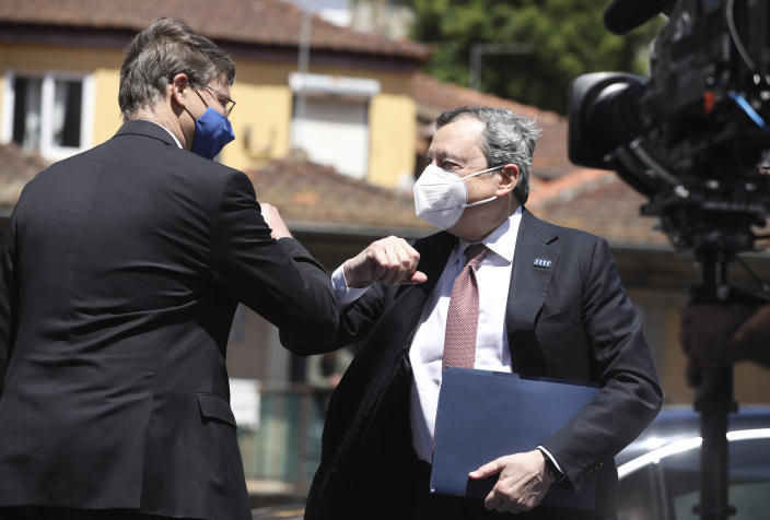 Italy's Prime Minister Mario Draghi, right, elbow bumps European Commissioner for An Economy that Works for People Valdis Dombrovskis as he arrives for an EU summit at the Alfandega do Porto Congress Center in Porto, Portugal, Friday, May 7, 2021. European Union leaders met for a summit in Portugal on Friday, sending a signal they see the threat from COVID-19 on their continent as waning amid a quickening vaccine rollout. Their talks hope to repair some of the damage the coronavirus has caused in the bloc, in such areas as welfare and employment. (Jose Coelho, Pool via AP)