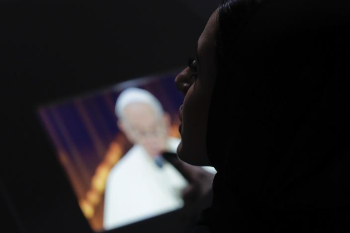 A woman looks at a monitor broadcasting the image of Pope Francis speaking during an Interreligious meeting at the Founder's Memorial in Abu Dhabi, United Arab Emirates, Monday, Feb. 4, 2019. Pope Francis arrived in Abu Dhabi on Sunday. His visit represents the first papal trip ever to the Arabian Peninsula, the birthplace of Islam. (AP Photo/Andrew Medichini)