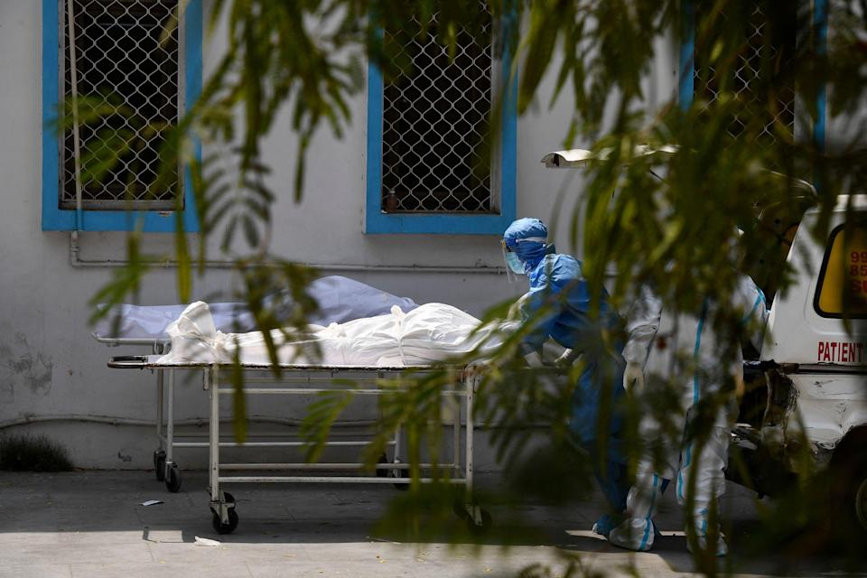<p>Representative: A medical staff prepares to transfer the body of a patient who died of the Covid-19 coronavirus disease into an ambulance at a mortuary in New Delhi on 29 April 2021</p> (Getty Images)