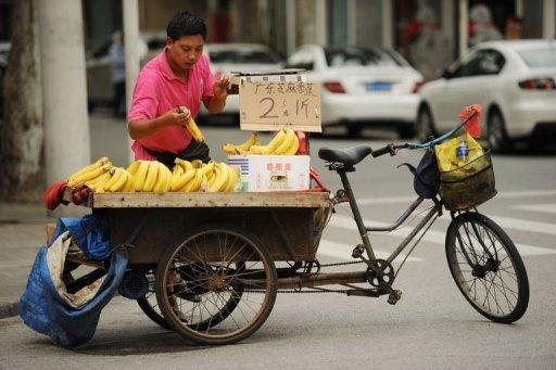 A vendor sells bananas from his tricycle on a street in Shanghai on July 9, 2012. China said on Friday its economy grew by 7.6 percent in the second quarter of 2012, the slowest pace in more than three years