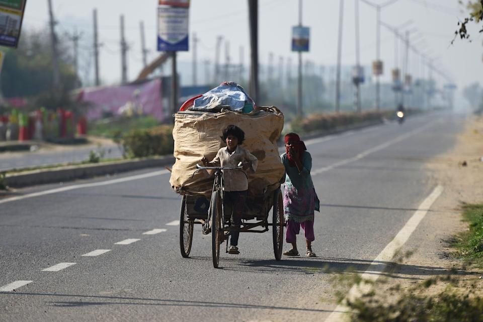 A child pulls a garbage cycle rickshaw as his mother pushes it along a street during Covid-19 curfew in Haryana on 22 March, 2020. (AFP via Getty Images)