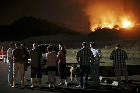 Residents watch a fast-moving wildfire approach in San Marcos, California May 14, 2014. REUTERS/Sandy Huffaker