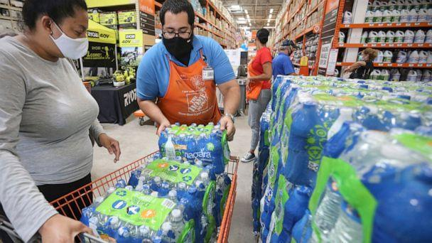 PHOTO: A Home Depot worker loads water bottles into a shopping cart as shoppers prepare for possible effects of tropical storm Elsa in Miami, July 3, 2021. (Al Diaz/AP)