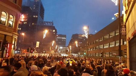 People watch as fire breaks out at an apartment block in Manchester, Britain December 30, 2017 in this image obtained from social media. TWITTER/@MANCTRAFFIC/via REUTERS.