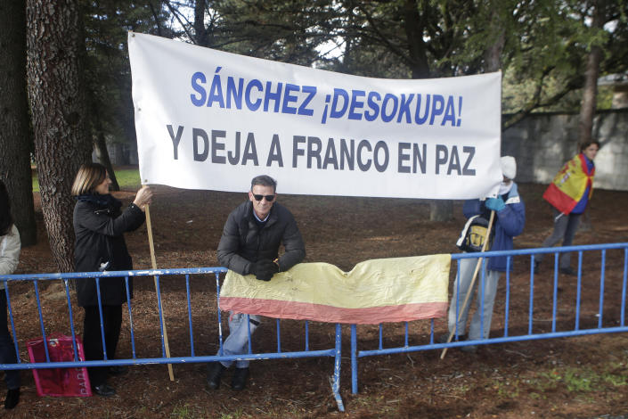 """People carrying a banner reading in Spanish """"Sanchez unworried. Leave Franco in Peace"""" stand outside the Fallen mausoleum near El Escorial, outskirts of Madrid, Thursday, Oct. 24, 2019. Forty-four years after his demise, the remains of Spanish dictator Gen. Francisco are to be dug out of his grandiose resting place outside Madrid and taken to a small family crypt, finally satisfying a long-standing demand of his victims' relatives and others who suffered under his regime. (AP Photo/Paul White)"""