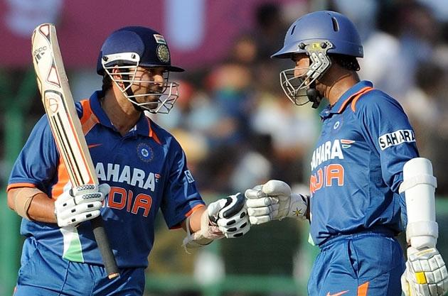 Indian cricketer Sachin Tendulkar and Dinesh Karthik bump fists during the second One Day International (ODI) cricket match at the Captain Roop Singh Stadium in Gwalior on February 24, 2010. India are currently 198 runs for the loss of one wicket after thirty overs after electing to bat first. AFP PHOTO/ MANAN VATSYAYANA