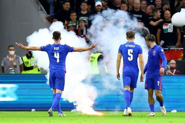 England's Declan Rice gestures towards the fans as a flare is thrown onto the pitch in Budapest