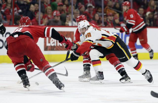 Carolina Hurricanes' Dougie Hamilton, left, and Jordan Martinook chase the puck with Calgary Flames' Elias Lindholm (28), of Sweden, during the second period of an NHL hockey game in Raleigh, N.C., Sunday, Feb. 3, 2019. (AP Photo/Gerry Broome)